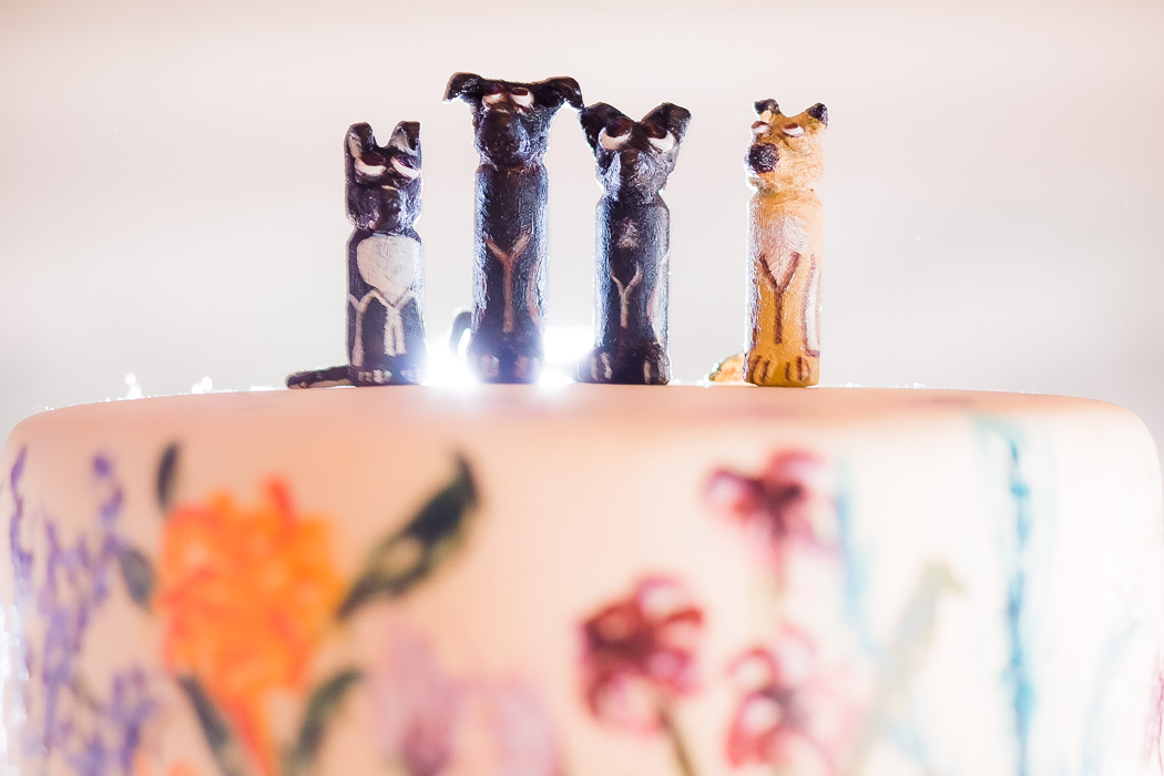 4 carved comical dogs sit atop a wedding cake