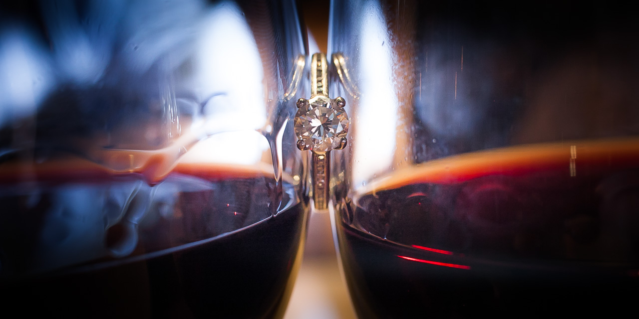 Two glasses of red wine suspend a engagement ring between them