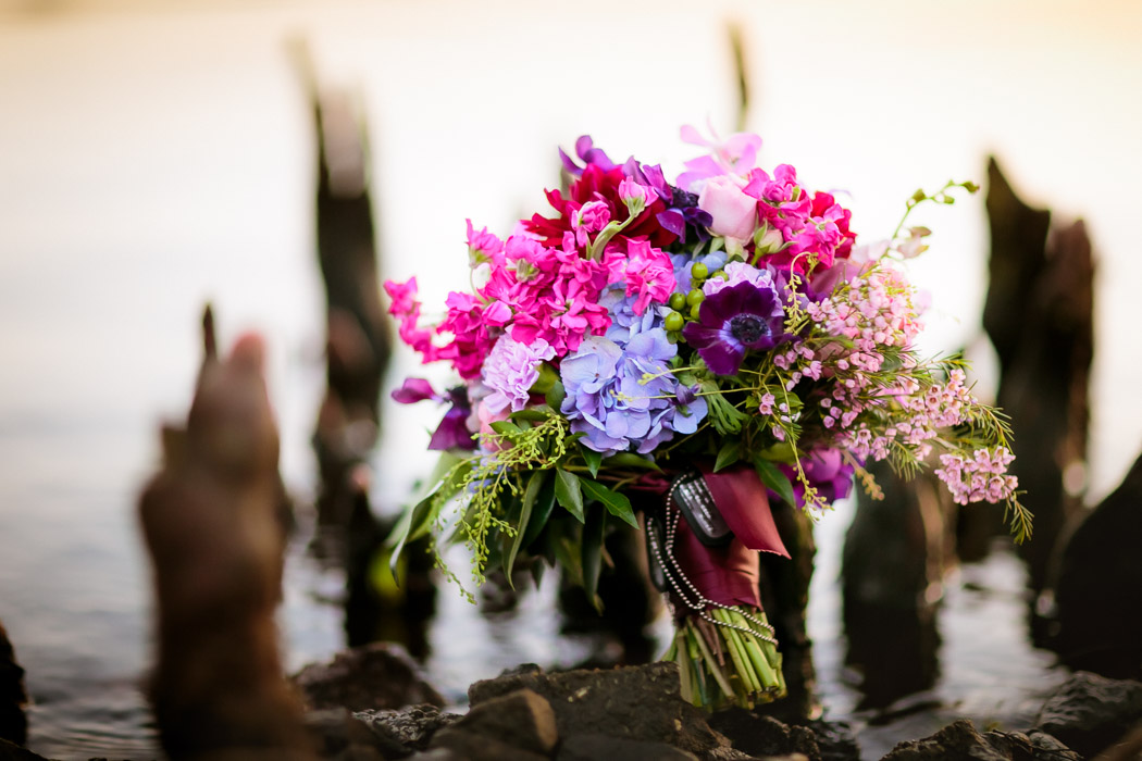 prink and purple hydrangea bouquet sits in swamp in beautiful and unusual wedding photograph