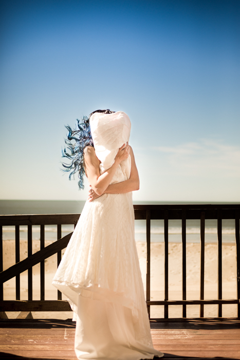 bride with blue hair holds her dress on the deck of her Oak Island wedding before getting ready