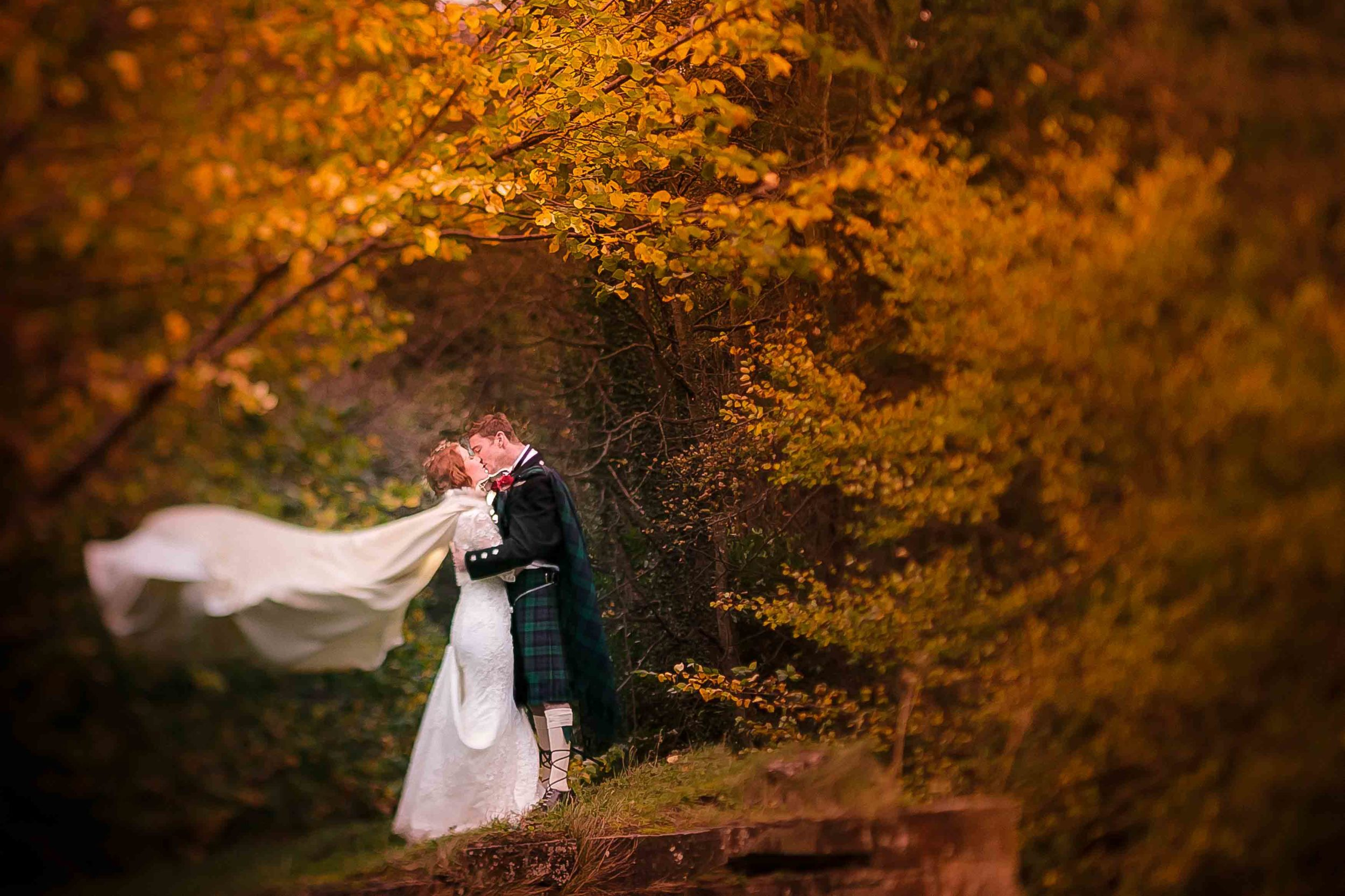 Scottish bride with flowing cape and kilted groom stand beneath orange trees.