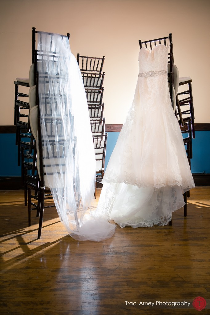 Dress shot with veil on stack of Chiavri chairs at their wedding at Millennium Center in Winston-Salem, NC.