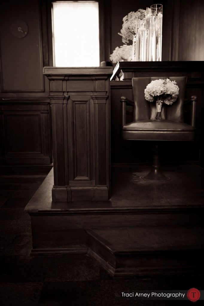 Bouquet sitting in witness chair in historic courthouse where their ceremony was taking place at their wedding at Millennium Center in Winston-Salem, NC.