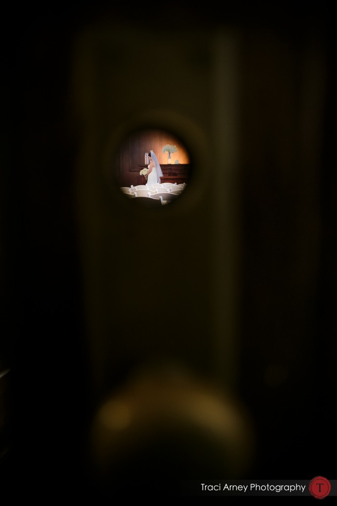 Shot of bride through key hole in historic courtroom at their wedding at Millennium Center in Winston-Salem, NC.