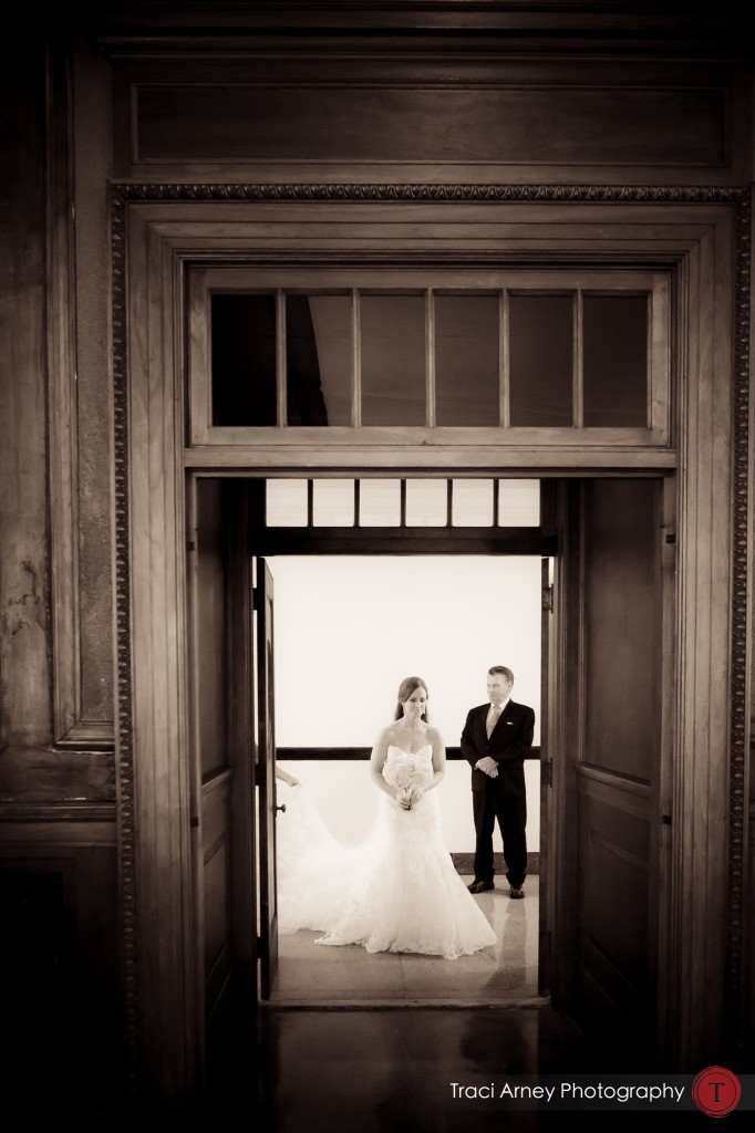 Bride and her father walk through beautiful doorway into historic courtroom at their wedding at Millennium Center in Winston-Salem, NC.