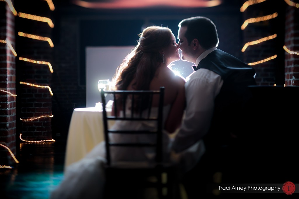 Bride and groom kiss at their sweetheart table at their wedding at Millennium Center in Winston-Salem, NC.