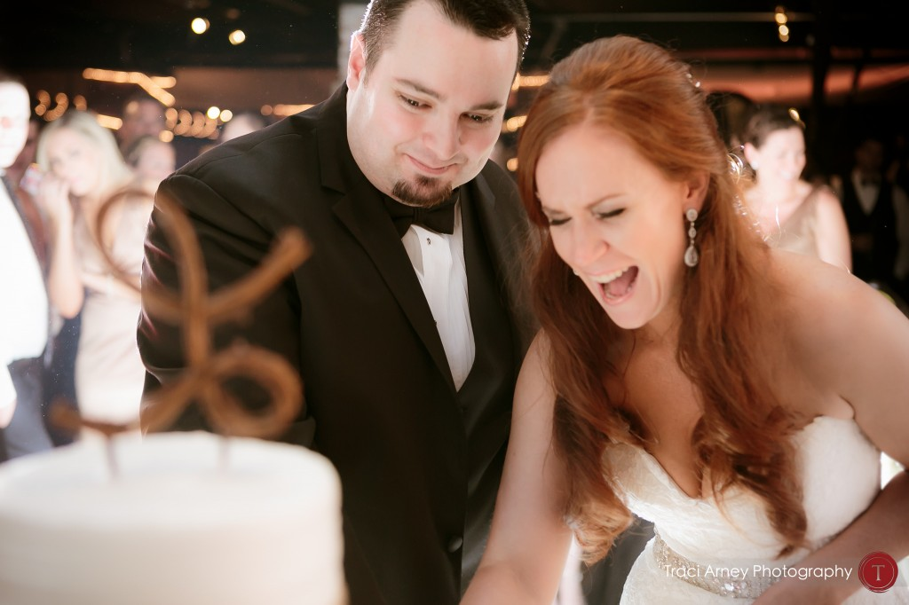 Bride and groom laugh as they cut their cake during their reception at their wedding at Millennium Center in Winston-Salem, NC.