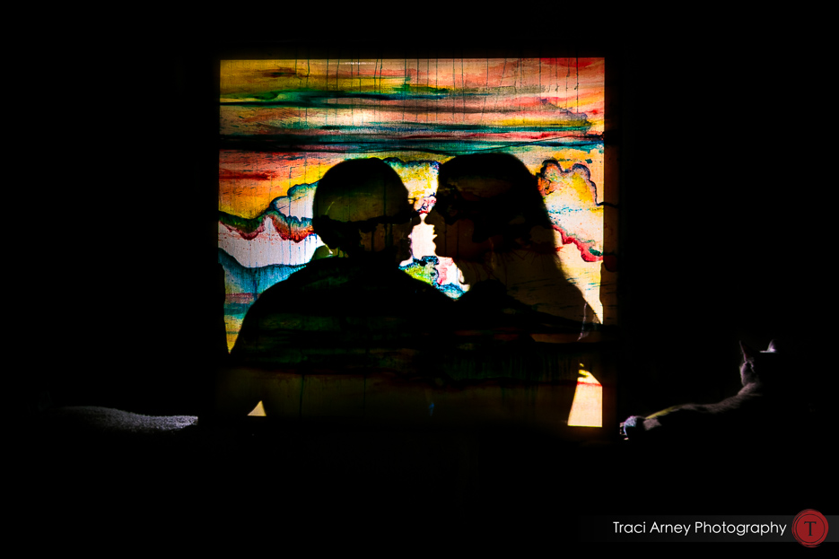 Engagement session in Greensboro, NC, bride and groom silhouetted behind colorful painting.