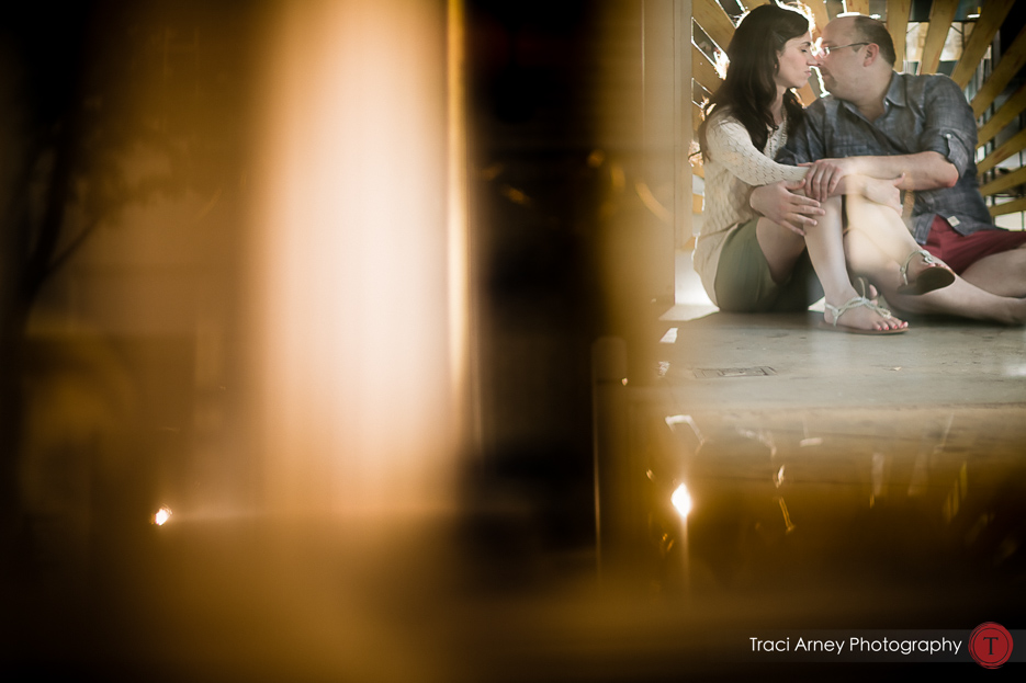 Engagement session in Greensboro, NC, bride and groom reflected in window while sitting on sidewalk