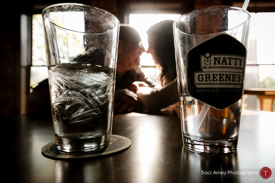 Engagement session in Greensboro, NC, bride and groom photographed cuddling between two glasses