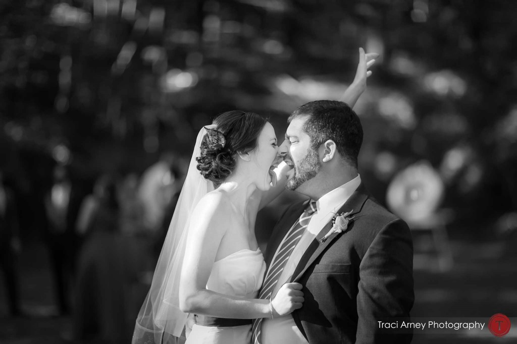 black and white candid of bride and groom joyfully embracing