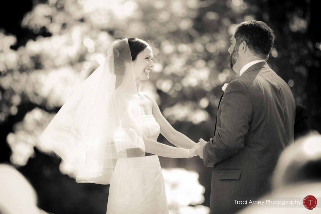 Black and white image of bride and groom holding hands during their wedding ceremony during their campground wedding in Asheville, NC.