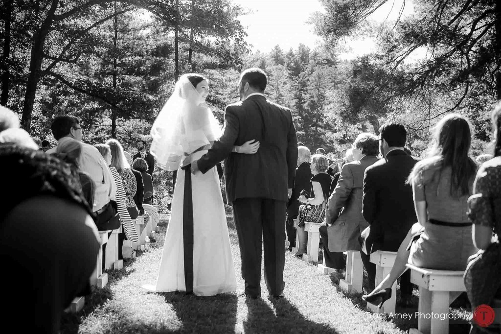 bride and groom walk down the aisle of their outdoor ceremony during their campground wedding in Asheville, NC.