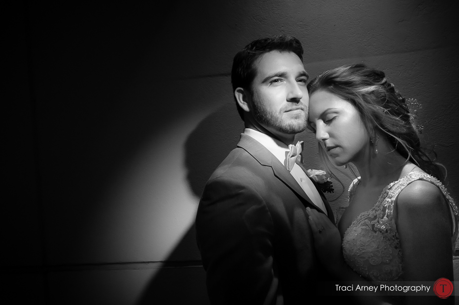 black and white portrait of bride and groom in dramatic lighting during romance session. Revolution Mills wedding.