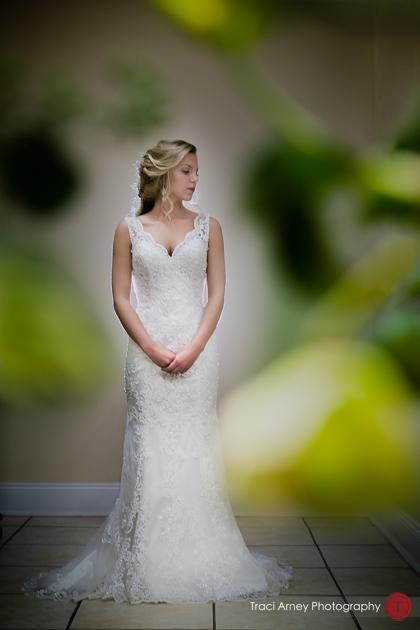 bride portrait shot through arrangement of flowers. Revolution Mills wedding.