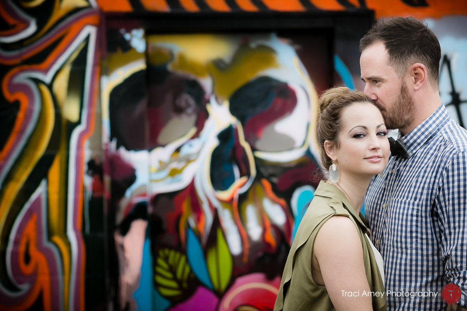 color portrait of fashionable engaged couple in front of colorful skull portrait engagement session, midwood, charlotte, NC