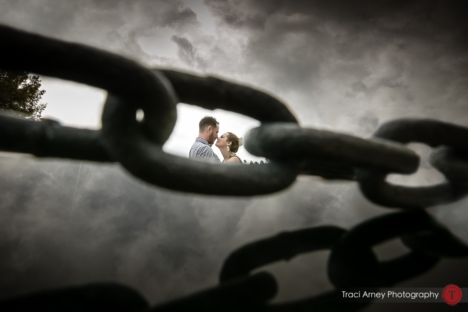 engaged couple framed in chain links with reflection engagement session, midwood, charlotte, NC