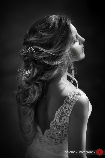 Beautifully lit, dramatic portrait of bride from the side showing back of dress and flowing hairstyle
