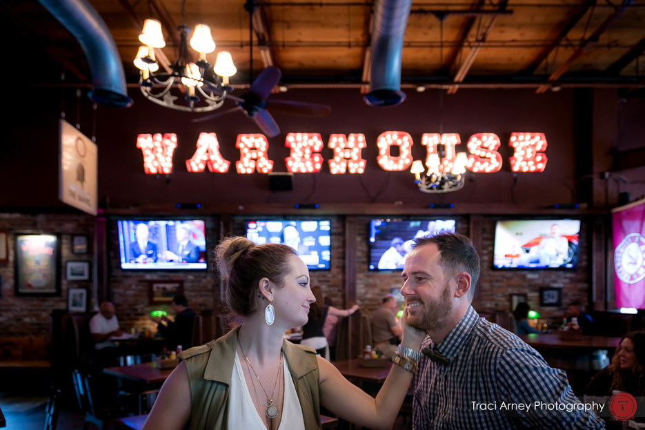 Engaged couple under WAREHOUSE sign in restaurant engagement session, midwood, charlotte, NC