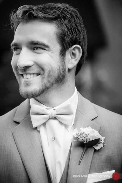 Black and white dynamic portrait of groom smiling. Revolution Mills wedding.