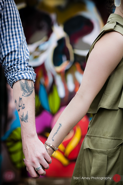 engaged couple with tattoos in front of skull tattoo parlor engagement session, midwood, charlotte, NC