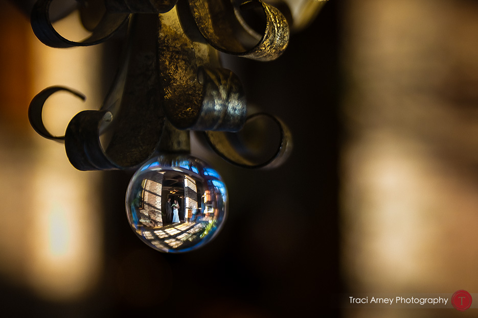 fine art photo of bride and father waiting to walk down the aisle shot through glass orb. Revolution Mills wedding.