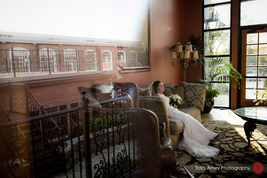 fine art photograph of bride waiting to walk down the aisle with a reflection of the mill in the shot. Revolution Mills wedding.