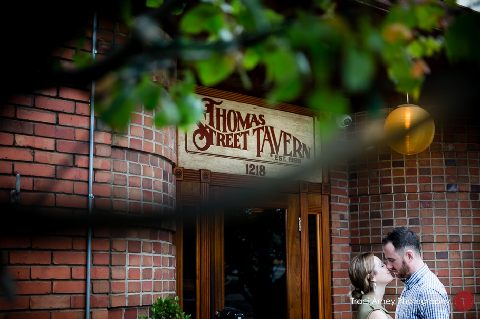 bride and groom shot through trees in front of Thomas Street Tavern in Midwood neighborhood, charlotte nc