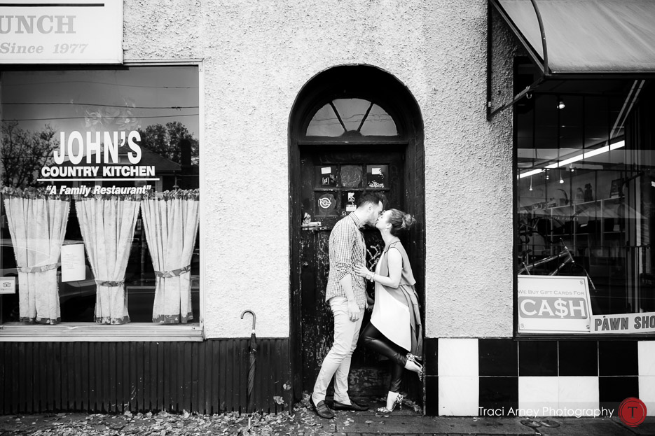 black and white portrait of engaged couple in doorway in Midwood neighborhood in Charlotte, NC