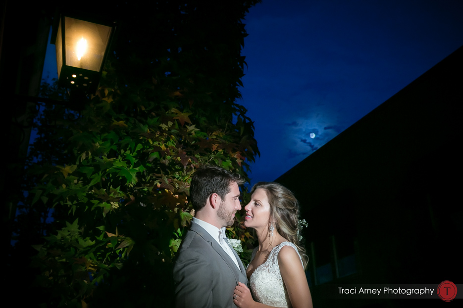 bride and groom against ivy in romance session with full moon behind them. Revolution Mills wedding.