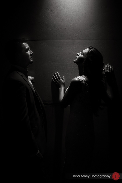 dramatically lit black and white fine art portrait of bride and groom in strong downlighting. Revolution Mills wedding.