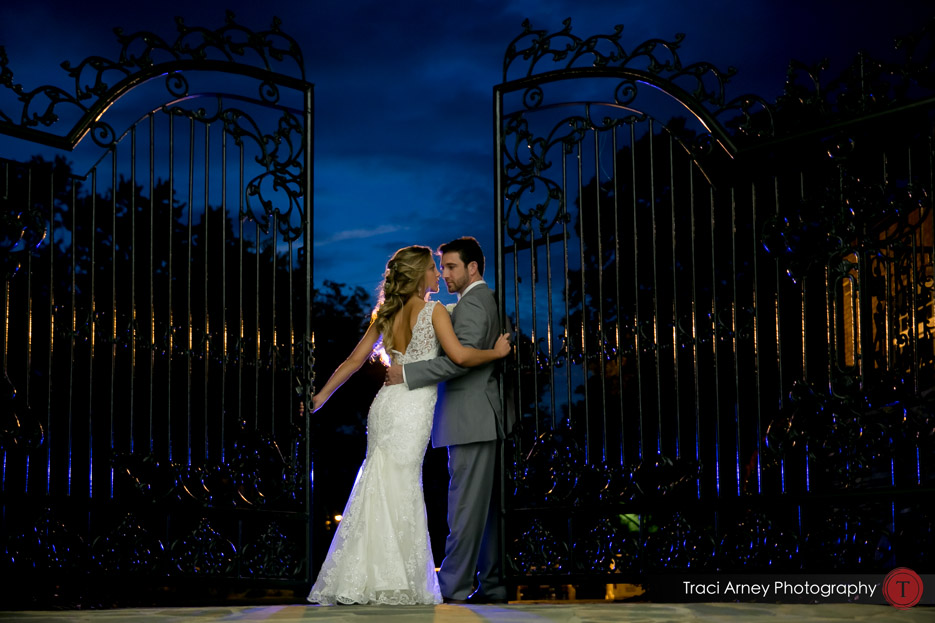 bride and groom between wrought iron gate against an intense blue night sky. Revolution Mills wedding.