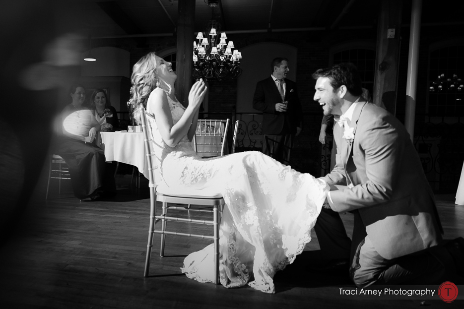 Black and white shot of garter with bothered and groom laughing Revolution Mills wedding.