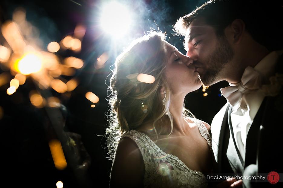 Bride and groom kiss during sparkler exit Revolution Mills wedding.