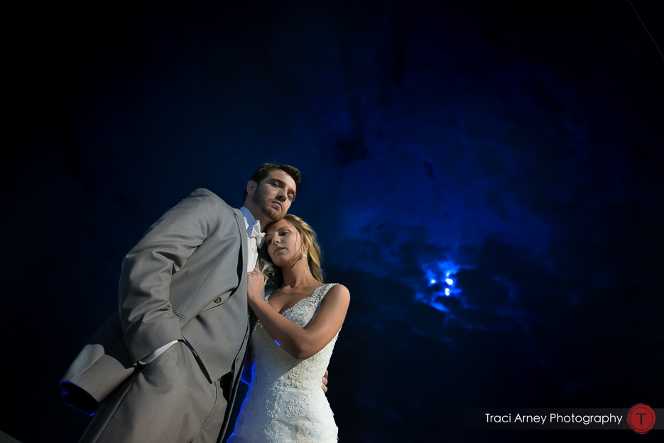 Low dramatic romantic romance session portrait of bride and groom again a cloudy sky with the moon showing through. Revolution Mills wedding.