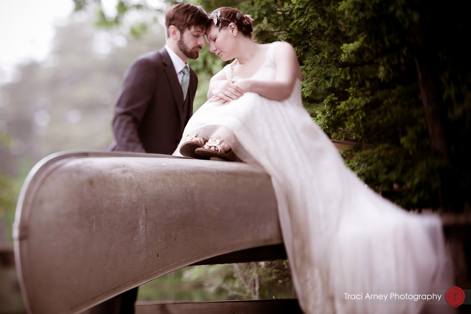 bride and groom sit on top of canoe in Camp Pinnacle outdoor campground wedding in Asheville, NC