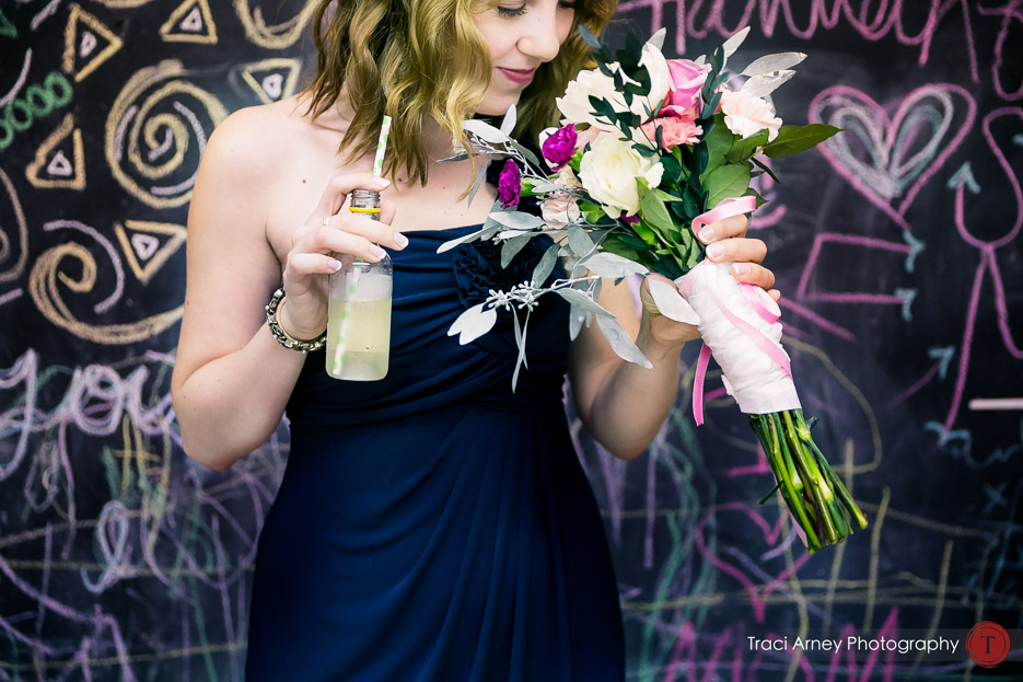 Bridesmaid holding bouquet, drinking a drink and standing in front of a colorful chalkboard wall at Camp Pinnacle outdoor campground wedding in Asheville, NC