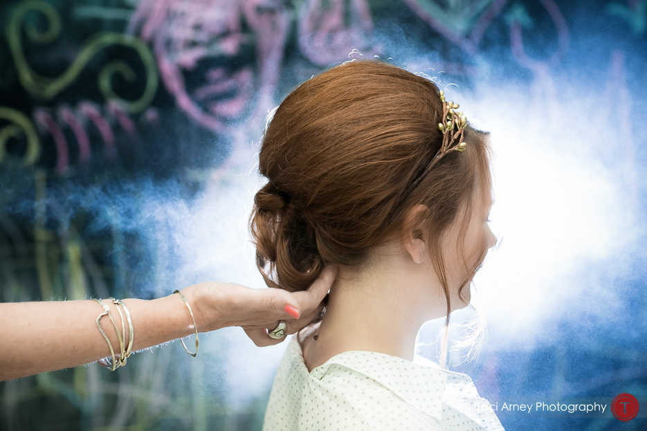 Bride getting her hair done with hairspray backlit against colorful chalkboard backdrop at Camp Pinnacle outdoor campground wedding in Asheville, NC