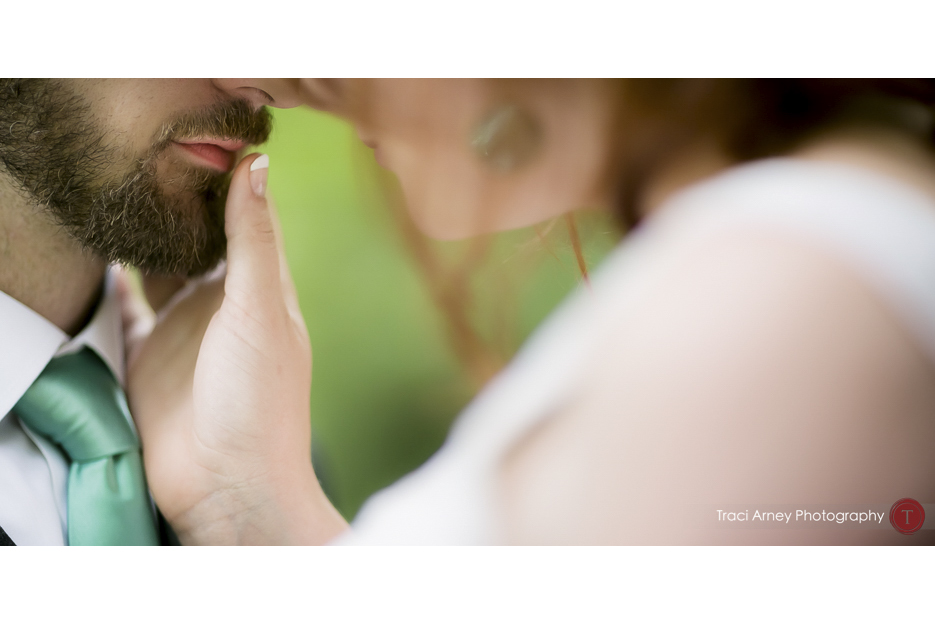 Color image of bride touching her groom's lips during their first look at Camp Pinnacle outdoor campground wedding in Asheville, NC