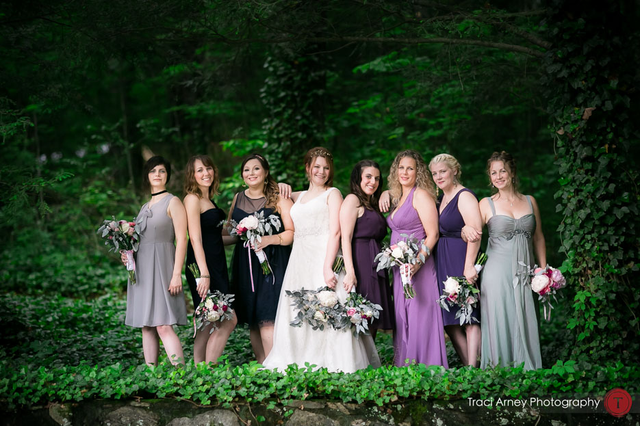 COlor image of bridesmaids in mismatched dresses standing in the forest at Camp Pinnacle outdoor campground wedding in Asheville, NC