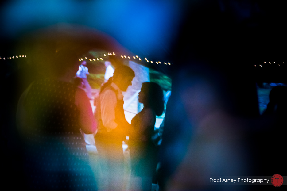 Reflection of bride and groom dancing on dace floor shot into colorful photograph at Camp Pinnacle outdoor campground wedding in Asheville, NC