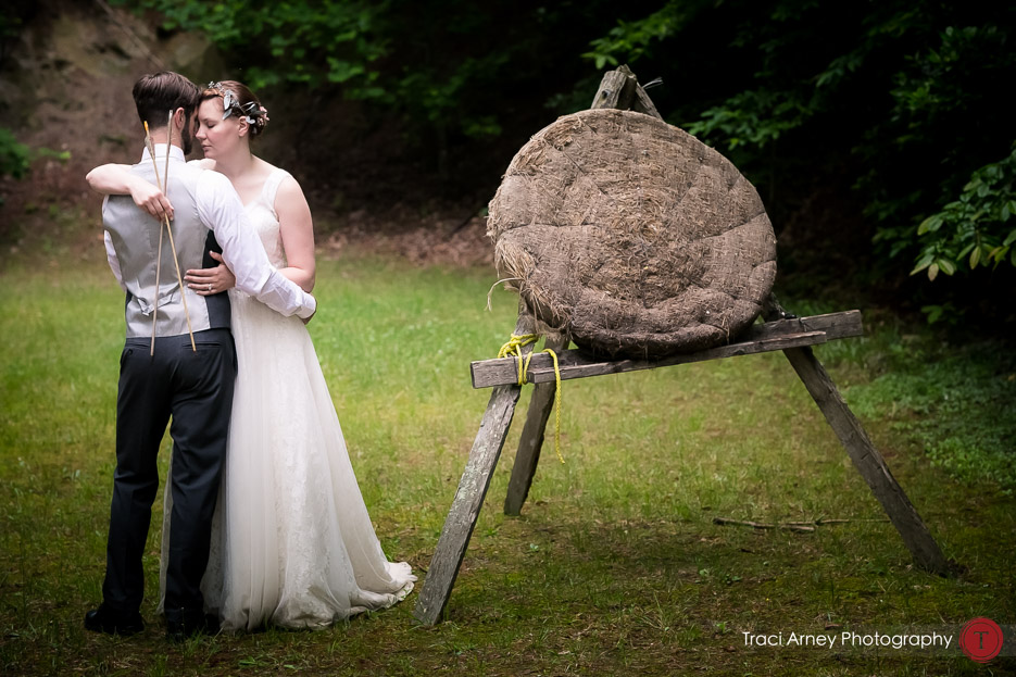 Bride and groom embrace with archery equipment on archery range in a day after session at Camp Pinnacle outdoor campground wedding in Asheville, NC