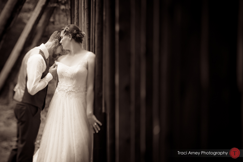 Sepia tone image of bride and groom embracing behind wooden wall in a day after session at Camp Pinnacle outdoor campground wedding in Asheville, NC