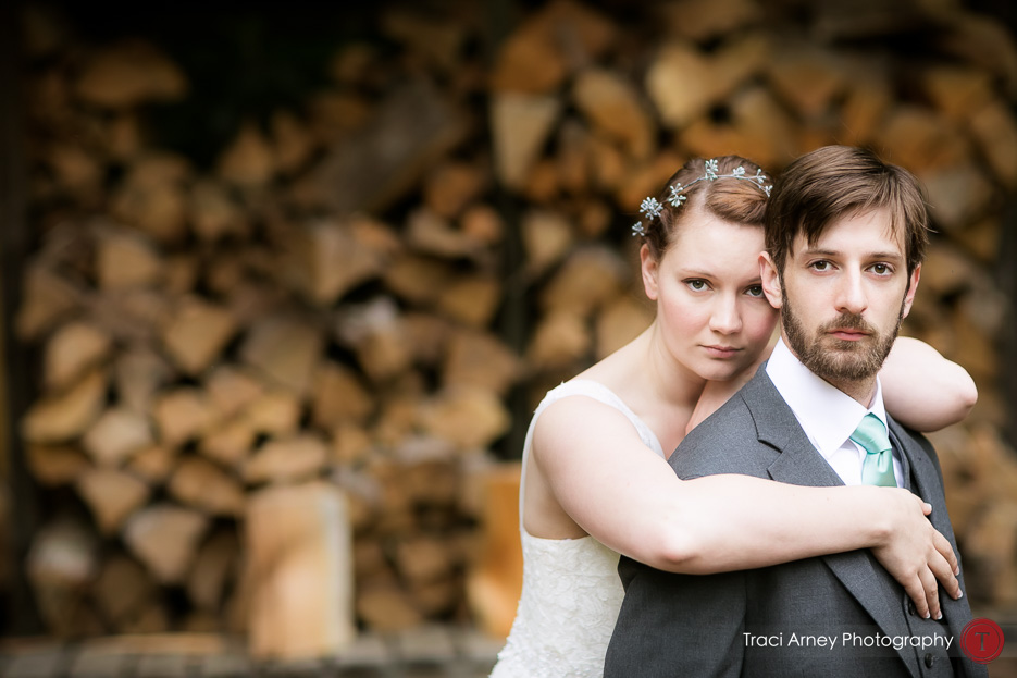 Bride and groom embrace and look at the camera in front of stacks of logs in a day after session at Camp Pinnacle outdoor campground wedding in Asheville, NC