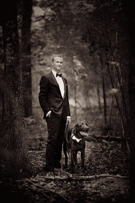 wedding portrait of groom and chocolate lab in forest